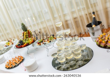 Table with cold snacks and tableware on luxury stand-up party, Champagne Pyramid - stock photo
