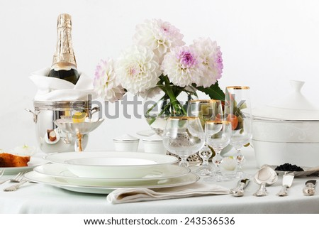 table with dishes and champagne on a white background - stock photo