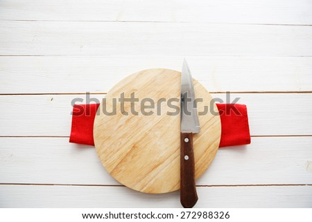 table with empty wooden cutting board and knife - stock photo