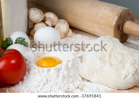 Table with fresh dough and heap of flour