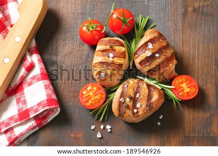 table with grilled pork medallion sprinkled with pepper and sea salt, accompanied with linen and sharp knife - stock photo