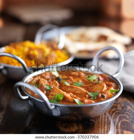 table with indian food and chicken curry in balti dishes - stock photo