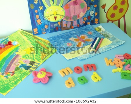 Table with paintings, crayons and colorful letters - stock photo
