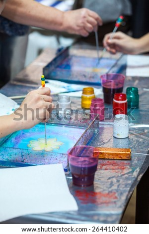 Table with paints stained for ebru marbling - stock photo