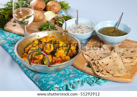 Table with typical Indian dishes such as Indian curry, roti and dips