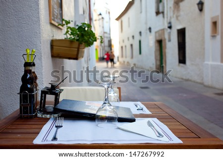 table with wine glasses at a summer outdoor cafe awaits visitors - stock photo