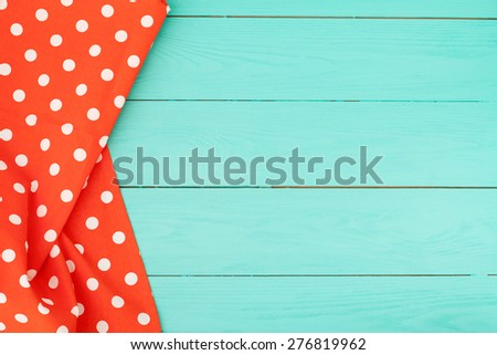 Tablecloth in polka dots on blue wooden background - stock photo