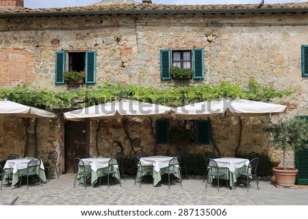 Tables and awnings outside an attractive Tuscan country restaurant. - stock photo