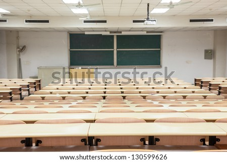 tables and chairs in a college classroom - stock photo