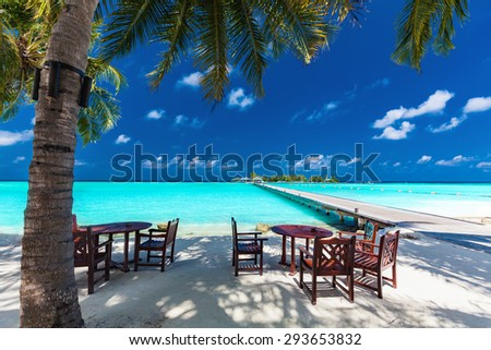 Tables and chairs in the shadow of palm tree on amazing tropical island - stock photo