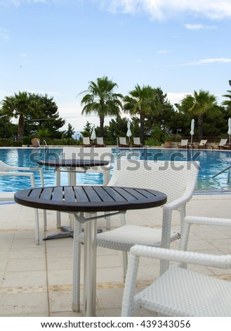 tables and chairs near the pool, table and chair near swimming pool in a tropical resort hotel, table and chairs near a cool pool in a hot  - stock photo