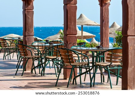 Tables and chairs near the sea beach - stock photo