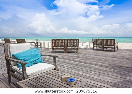 Tables and chairs on a wooden balcony of a restaurant on the beach with view over turquoise ocean. - stock photo