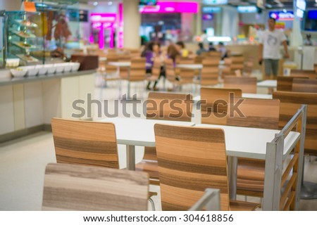 Tables and chairs on food court in huge mall
