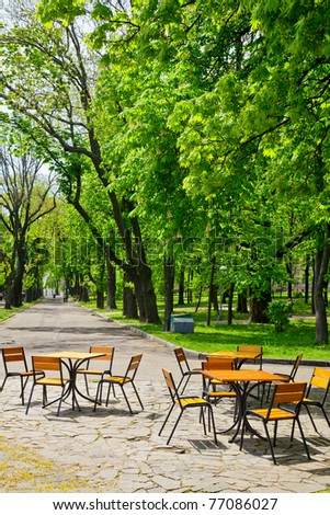 Tables and chairs under the blooming Chestnut tree at spring park - stock photo