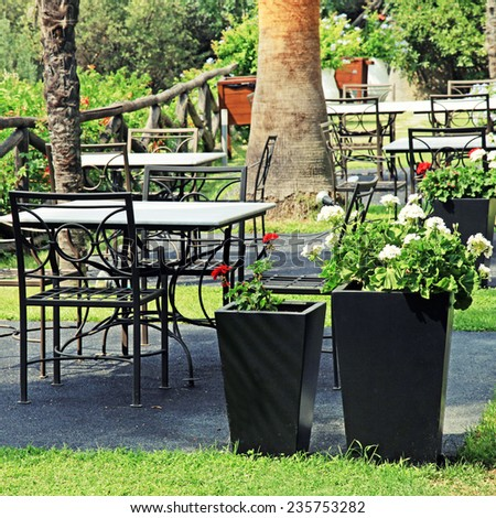 Tables and iron chairs on terrace with flower pots and beautiful garden view (Greece), square image - stock photo