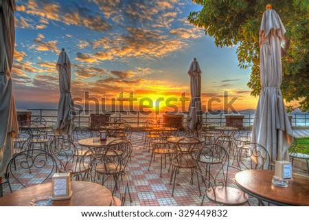 tables, chairs and umbrella in Alghero seafront at sunset, Italy - stock photo