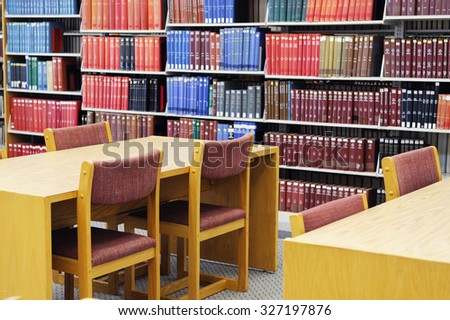 tables, chairs, bookshelf and books inside library - stock photo