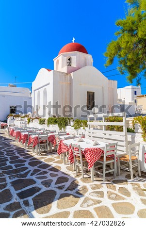 Tables in a tavern in front of typical church in Mykonos town, Cyclades, Greece - stock photo