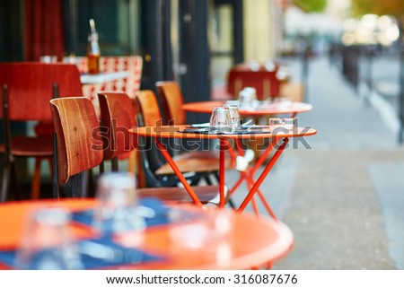 Tables of traditional outdoor French cafe in Paris - stock photo