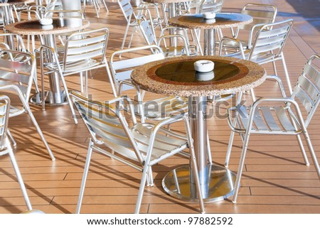 tables with ashtrays in outdoor bar on stern of cruise liner - stock photo