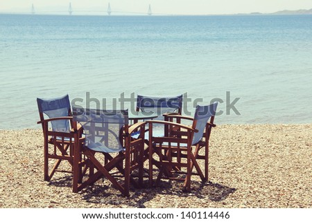 Tables with blue chairs in front of a turquoise sea in Nafpaktos in Greece
