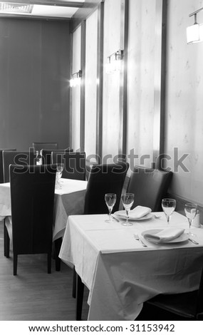 Tables with cutlery, plates and glasses in Restaurant