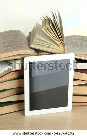 Tablet and books on light background