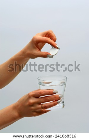Tablet and glass of water in female hands - stock photo