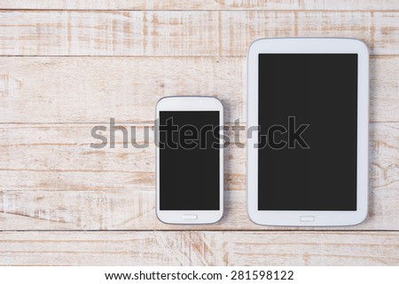 Tablet and phone  on white wood.Copy space - stock photo