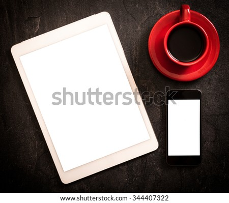 Tablet and smart phone with blank screens on dark background  - stock photo