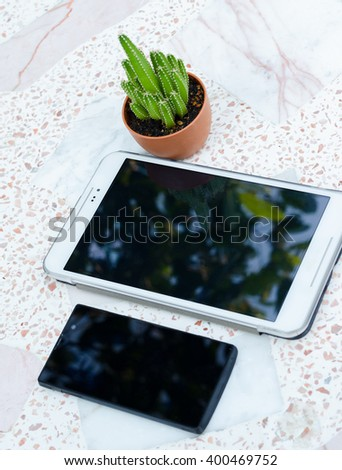 tablet and smart phone with coffee cup and cactus on stone table