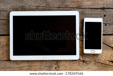 Tablet and smartphone on an old wood - stock photo
