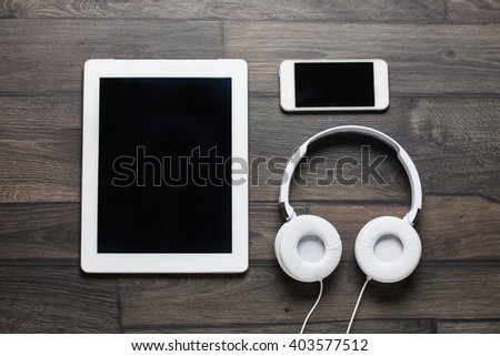 Tablet and smartphone on an old wood with headphones - stock photo