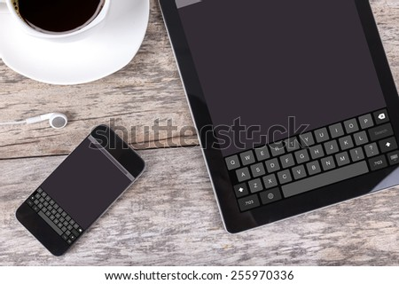 tablet and smartphone with keyboard on screen - stock photo