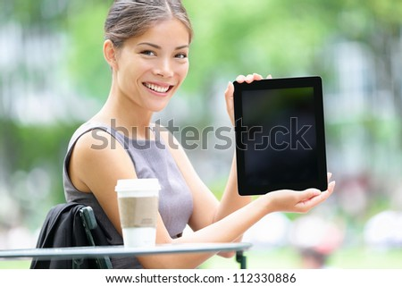 Tablet business woman showing display screen sitting in park. Beautiful young professional businesswoman smiling happy. Mixed race female model. Photo from Bryant Park, Manhattan, New York City. - stock photo