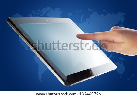 tablet computer and a hand on blue background with world map - stock photo