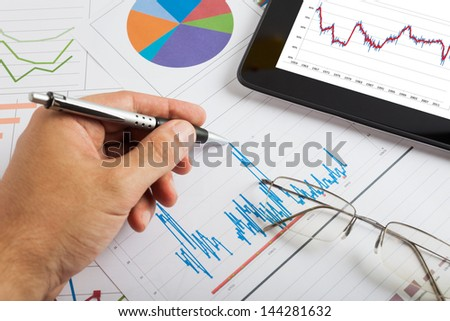 Tablet computer and financial charts - stock photo