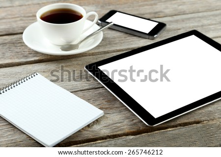 Tablet computer and touch screen smartphone with notebook and cup of coffee on grey wooden background - stock photo