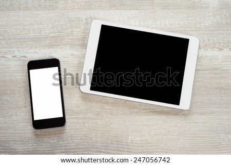 Tablet computer and white smart phone with isolated screens - stock photo