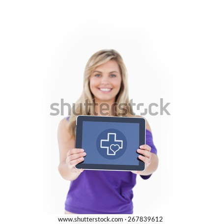 Tablet computer being held by a blonde woman against heart and cross - stock photo