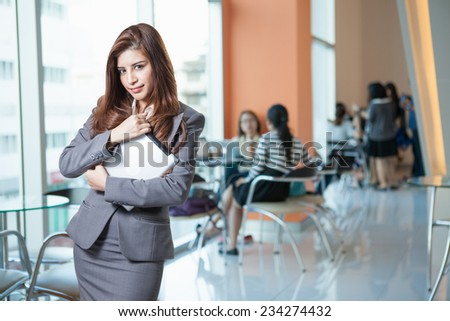 Tablet computer. Businesswoman using digital tablet happy isolated onoffice background. Beautiful mixed race Asian with finger on touch screen display. - stock photo