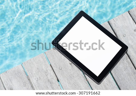 Tablet computer by the pool - stock photo