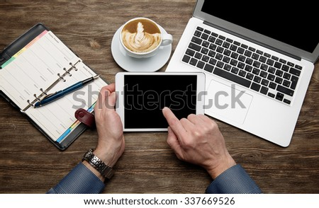 Tablet computer in male hands, cup of coffee, organizer,  laptop on a wooden table/ - stock photo