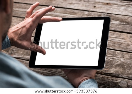 Tablet computer  in male hands over table. Clipping path included.