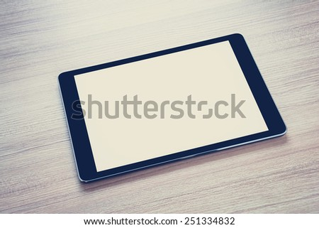 Tablet computer (isolated screen) on wooden table - vintage & retro style color effect - stock photo