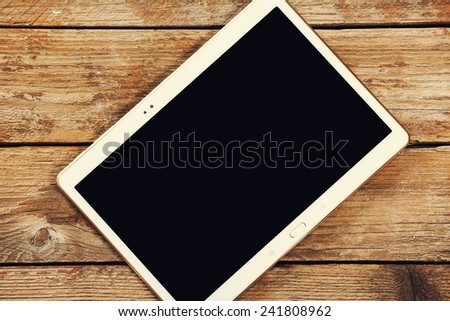 Tablet computer on a wooden background - stock photo