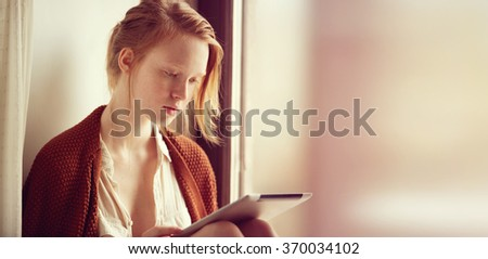 Tablet computer. Relaxed young mixed race woman in sofa smiling content, happy and reading on tablet pc at home. Lifestyle image of beautiful ?aucasian redhead and freckled girl relaxing. - stock photo