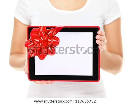 Tablet computer screen gift. Closeup of touch pad tablet computer screen with red gift ribbon. Christmas gift or present isolated on white background. - stock photo