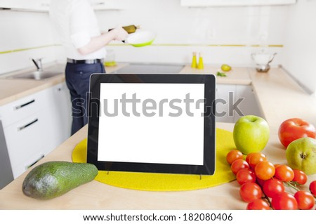 Tablet computer with blank screen in the kitchen - man cooking - stock photo